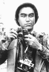 取材中にカメラを持つ沢田教一((C)グループ現代、共同)