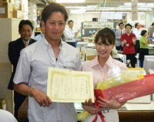婚姻届受理証明書と花束を手に、職員らから祝福を受ける大嶺祐太(左)と琴菜さん=石垣市役所