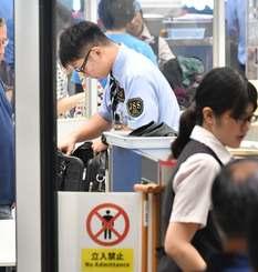 乗客の荷物を念入りに調べる保安検査場の係員=19日午後3時40分