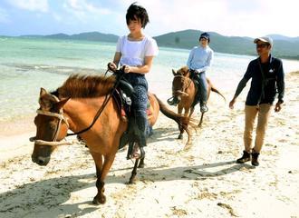 久米島馬牧場で人気の砂浜を歩くコース。井上福太郎さんがそばにつくが、客は自ら手綱をさばく=7月30日、同町謝名堂