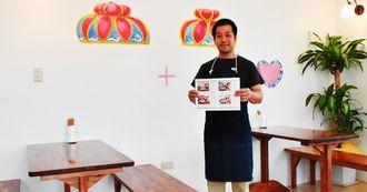 花笠をモチーフにしたカフェ風の店内で笑顔を見せる店長の前原秀志さん=20日、浦添市港川