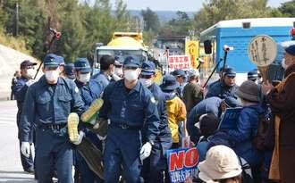国道に並ぶミキサー車などの基地内進入のため、新基地建設に反対する市民らを排除する県警機動隊員ら=14日正午ごろ、名護市辺野古の米軍キャンプ・シュワブゲート前