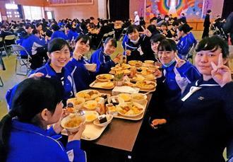 豪華な給食を友達同士で楽しそうに食べる3年生=2月13日、読谷村・古堅中体育館