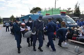 ゲート前に座り込んで抗議する市民らを強制排除する機動隊員=15日午前、名護市辺野古の米軍キャンプ・シュワブゲート前