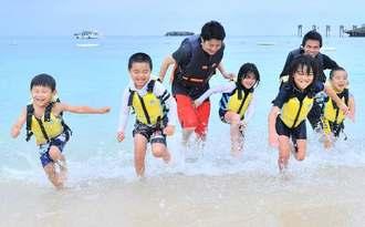 波打ち際で遊ぶ子どもたち=3日午前、恩納村・ANAインターコンチネンタル万座ビーチリゾート(下地広也撮影)
