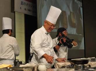 モニターに映る料理を解説する桑原友則総料理長=29日、糸満市・サザンビーチホテル&リゾート沖縄