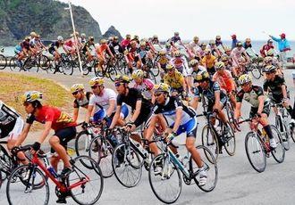 山岳コースへの入り口で一気にコーナリングする市民レース140キロの選手たち=国頭村与那(金城健太撮影)