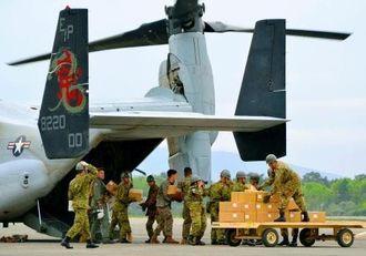 段ボールに入った救援物資をオスプレイに積み込む自衛官と米海兵隊員=18日、熊本県益城町・陸上自衛隊高遊原分屯地(新垣卓也撮影)