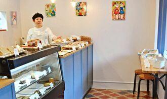 オーナーパティシエの比嘉みどりさん。手塗りした床や壁掛けの絵もお気に入り=7日、浦添市城間・菓子工房mimi