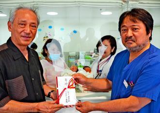 病院で生まれた赤ちゃんを背に沖縄タイムスの豊平社長(左)に100万円を寄付する上村院長=19日、中城村・うえむら病院