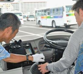 沖縄労働局と県バス協会が実施したバス運転手セミナーで、実際に運転を体験する参加者(右)=5月29日、豊見城市内