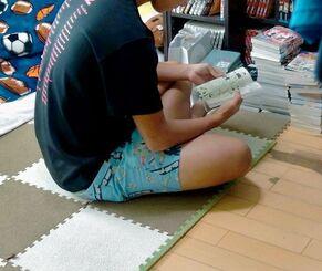 片付いた自室で漫画を読むショウタさん。高校生になった今は友達を招くこともあり「掃除は苦手だけど、自分の趣味を集めて居心地良くしている」と話す=8月、沖縄本島南部の公営住宅