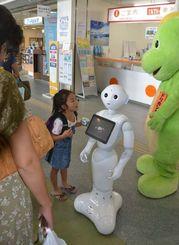 観光で訪れた子どもに話し掛けられる人型ロボットのペッパー君=石垣港離島ターミナル
