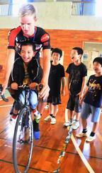 オランダチームの自転車に乗って喜ぶ子どもたち=9日、名護市・屋我地ひるぎ学園