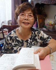 安室奈美恵さんが在籍したクラスの卒業文集をめくる仲座包子さん。「あなたは沖縄の宝よ」と呼び掛けた=8月、中城村内の自宅