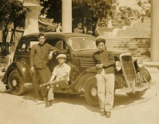 波上宮前でフォードと写る宜保弘助さん(左)=1934年ごろ(豊見城市教委提供)