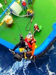船員に引き上げられた後、海保のヘリに救助される女性=30日、神山島灯台の南東4キロ沖合(第11管区海上保安本部提供)