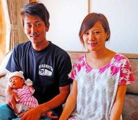 MESHヘリの搬送で無事に出産ができたと報告した知念夫妻と娘の愛寿ちゃん=伊江村西江上の知念さん宅