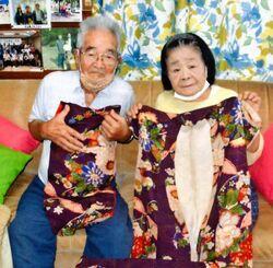 母が大切に保管していた着物と帯を手にする大田吉子さん、孝全さん夫妻=国頭村奥間