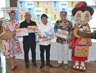 「沖縄シーサイドストーリー」をPRする(右から)マハエちゃん、OCVBの平良朝敬会長、ナンポーの具志堅全友専務ら=那覇空港ターミナル