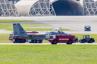 米軍嘉手納基地に緊急着陸した同基地所属のF15戦闘機。着陸後、緊急車両が囲み、機体を点検する様子が確認された=18日午前11時ごろ、同基地(読者提供)