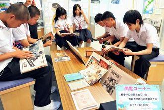 企画展閲覧コーナーで、戦時中の雑誌を見る修学旅行生たち=2日、糸満市摩文仁の沖縄県平和祈念資料館