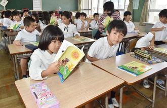 新しい教科書に興味津々の子どもたち=7日午前、那覇市・若狭小学校