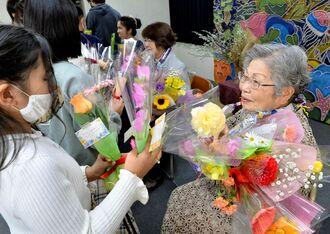 在校生や家族から花束で祝福される小田ミヅエさんら卒業生=那覇市樋川、珊瑚舎スコーレ