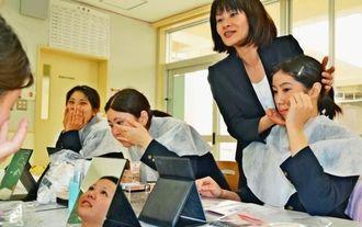 資生堂の阿部薫さん(右から2人目)にメークのポイントを教わる高校生ら=26日、浦添商業高校