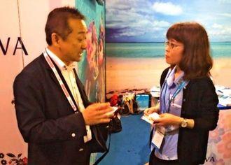 中国の観光関連業者(左)から質問を受けるメルキュールホテル沖縄那覇の担当者=上海展覧センター