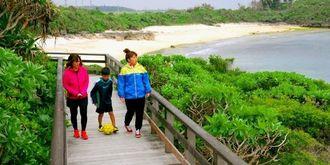波音が心地よい海沿いの遊歩道を歩く親子連れ=宮古島市平良狩俣の健康ふれあいランド公園