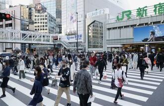 マスク姿でJR新宿駅前の横断歩道を行き交う人たち=21日午後