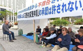 仲井真弘多知事の辺野古変更申請の承認に対し、座り込みで抗議する反対の市民=7日午後、那覇市の県民広場