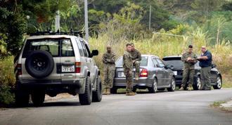 ヘリが上空を旋回した付近で話し合う米軍関係者ら=8日午後4時分、宜野座村城原区