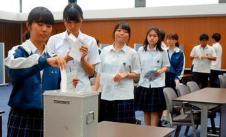 県知事選の模擬投票で1票を投じる昭和薬科大付属高校3年の生徒たち=27日、同校