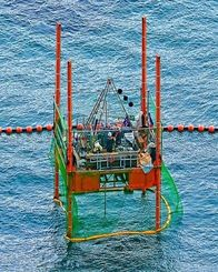 スパット台船から海底に杭を下ろしボーリング調査の作業を行う作業員=18日午後5時5分、名護市辺野古沖(本社チャーターヘリから古謝克公撮影)