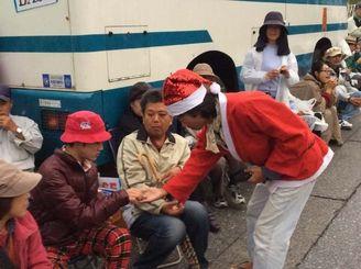 サンタクロースに扮して参加者にお菓子を振る舞う市民=25日午前7時半ごろ、名護市辺野古・キャンプシュワブゲート前