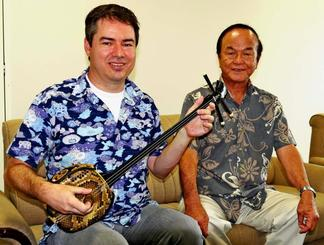 三線を手にするキース・ウィンターズさん(左)と師匠の比嘉義勝さん=4日、沖縄タイムス社