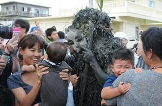 厄払いの泥を住民らに塗りたくるパーントゥ=25日、宮古島市平良島尻