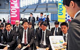 人事担当者(右端)の説明を熱心に聞く学生たち=14日、宜野湾市・沖縄コンベンションセンター