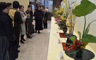 「花を通じて友好を」をテーマに約90点の作品が並んでいる=25日、那覇市久茂地のタイムスビル