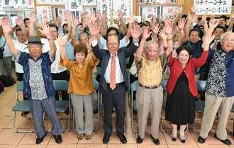 早々と当確が出て、支持者と万歳で喜ぶ照屋寛徳氏(中央)=22日午後8時1分、宜野湾市長田の選挙事務所