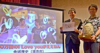 グランプリを受賞した金城康史さん(右)と池田龍丙さん。左は受賞作品=3日、読谷村・沖縄残波岬ロイヤルホテル