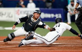 9回オリックス2死二塁、ジョーンズの右前打で本塁を突いた代走太田をタッチアウトにするロッテの捕手田村=京セラドーム