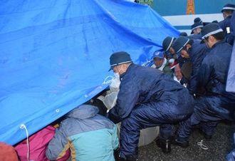 雨の中、ブルーシートを雨よけにして座り込む市民らを排除する県警や警視庁機動隊員ら=7日午前7時すぎ、名護市辺野古の米軍キャンプ・シュワブのゲート前