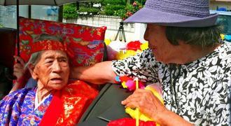 「おめでとう」といとこの金城敏子さん(写真右)から声を掛けられる又吉千代さん=名護市、安部公民館前