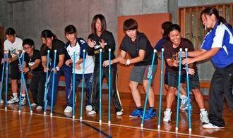 スティックを使用した福祉レクをする沖大の学生ら=沖縄大体育館