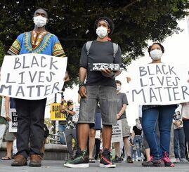 プラカードで黒人の命を守るよう訴える集会参加者=12日、沖縄市・胡屋十字路
