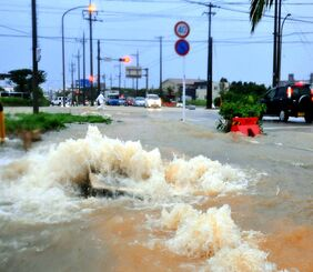 大雨で道路が冠水し、排水溝から水が溢れだした市街地=6月8日、石垣市