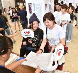 安室奈美恵さん引退の日の朝刊を買い求めるファン=16日午前、那覇市・沖縄タイムス社